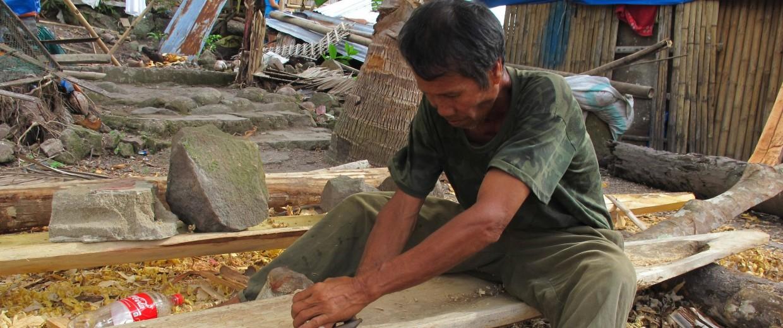 Image: Fisherman Charito Badong shapes the hard wood of a tree blown down by Typhoon Haiyan into a hull for his new fishing boat in Botlog Daku