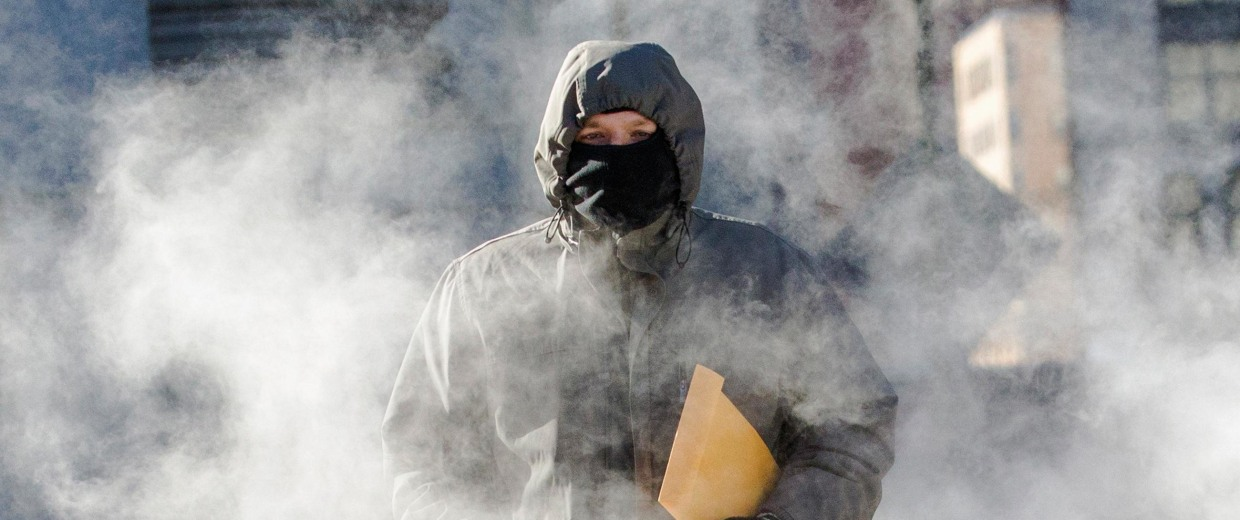 Image: A man walks through a steam cloud in frigid cold temperatures in the downtown section of Manhattan, New York