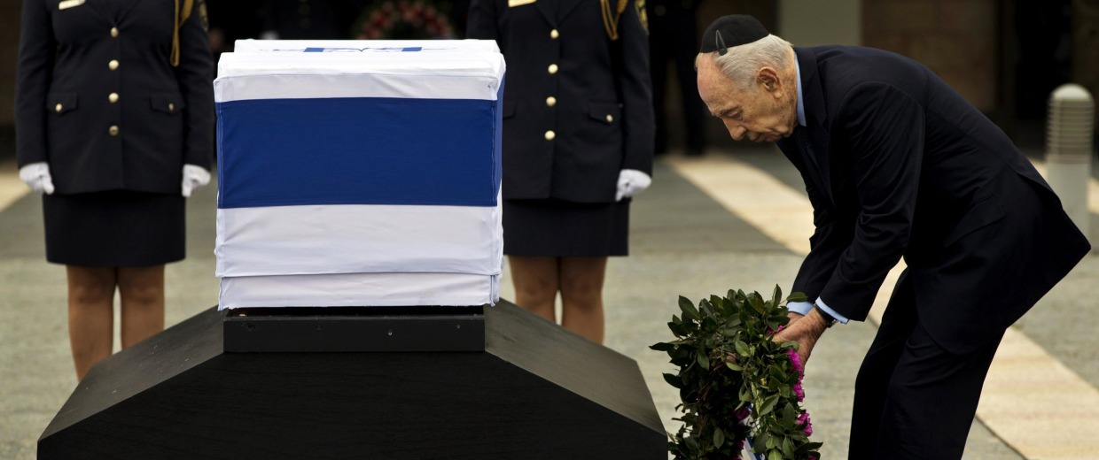 Israel's President Shimon Peres lays a wreath next the coffin of late Israeli Prime Minister Ariel Sharon at the Knesset Plaza, Israeli Parliament, in Jerusalem.