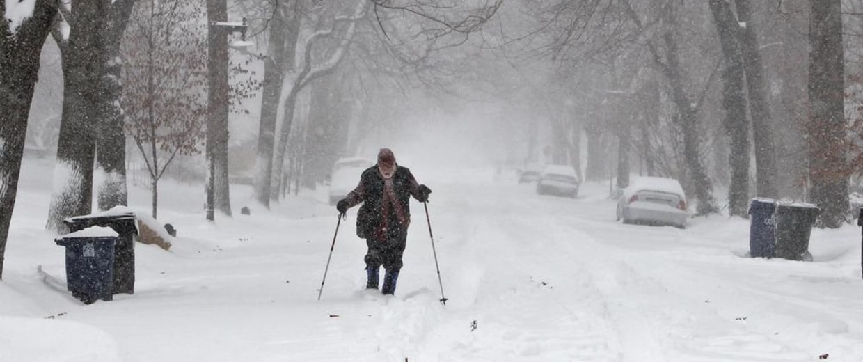 Image: Ray Pass gets a chance to use his cross country skis on a street in University City, Missouri.