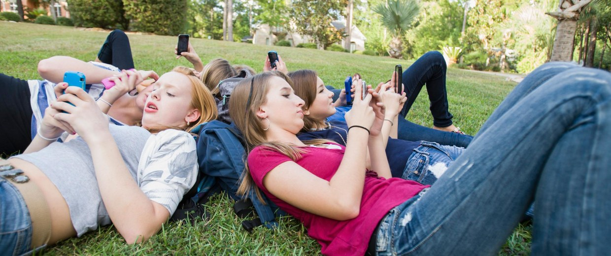 Image: Teen girls text on their phones.