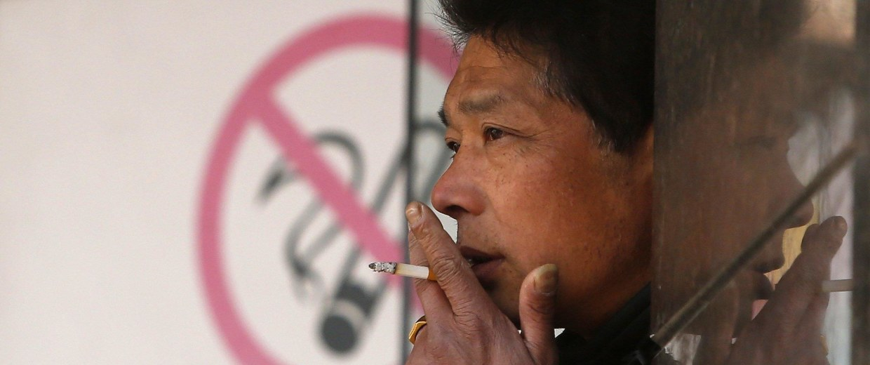 """Image: A man smokes in front of a """"no smoking"""" sign outside a shopping mall in Shanghai"""