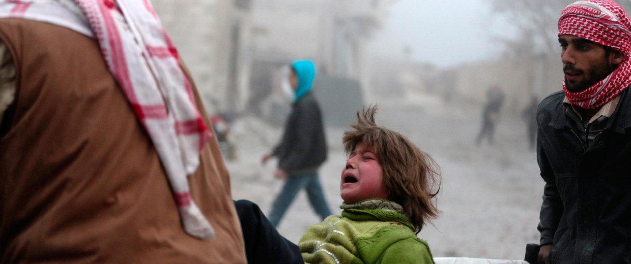 Image: A boy reacts as he is carried on a stretcher at a damaged site after what activists said was heavy shelling by forces loyal to Syrian President Bashar Al-Assad in Duma, Damascus