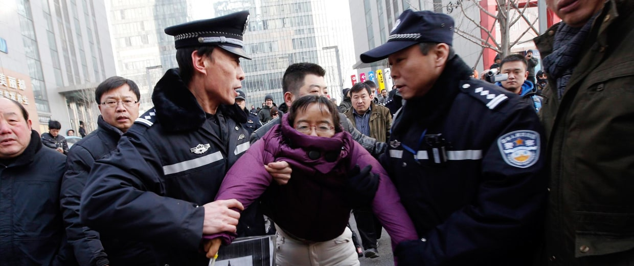 Image: Liu Chunxia, a supporter of Xu Zhiyong is detained by policemen while she gathers with other supporters nearby a court where Xu's trial is being held in Beijing