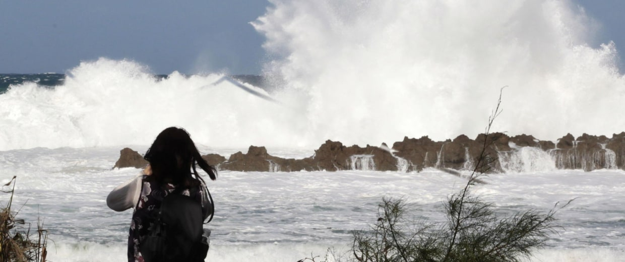 Image: A woman watches large waves crash onto the shore at Shark's Cove as high surf hits the north shore of Hawaii.