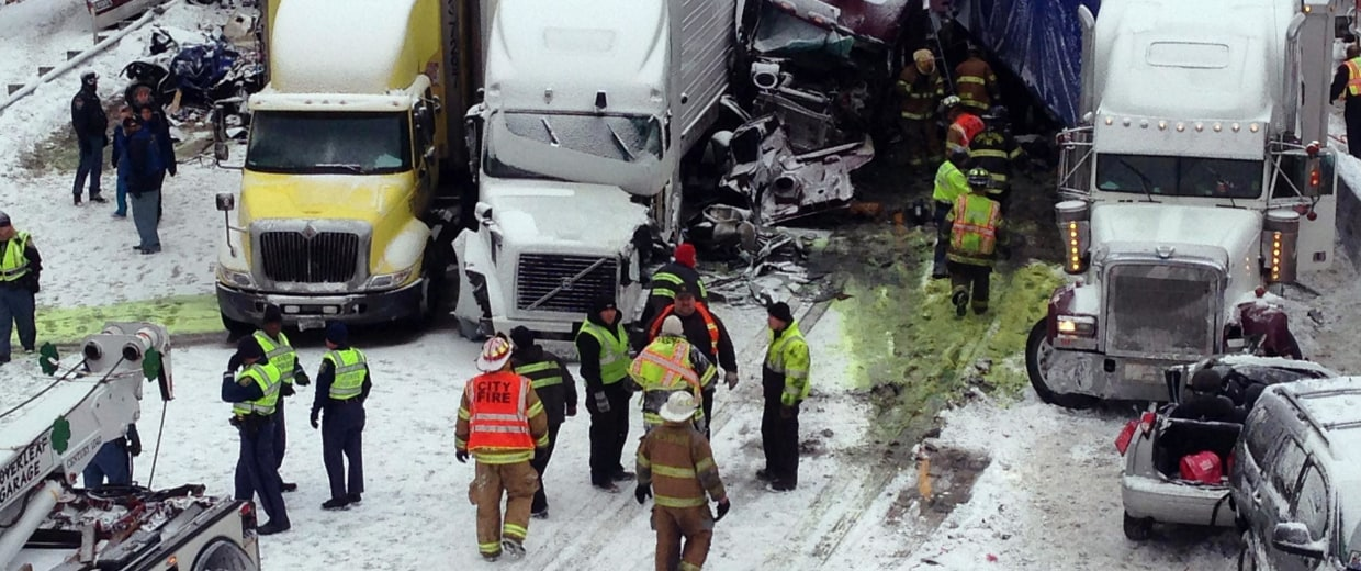 Image: Emergency crews work at the scene of a massive pileup