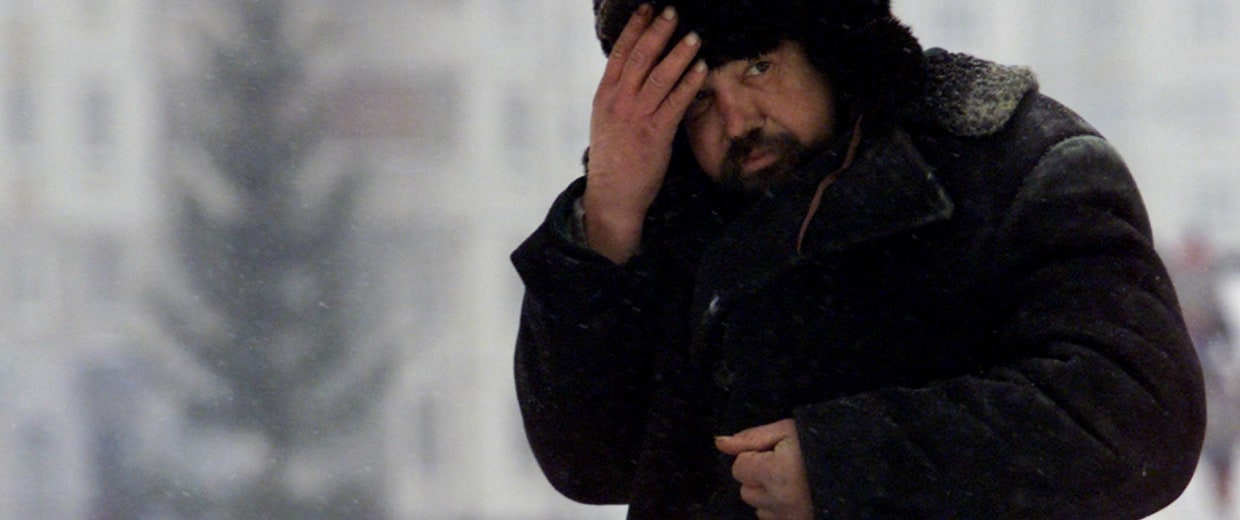 A homeless man warms himself up with a mixture of vodka and beer in a Moscow
