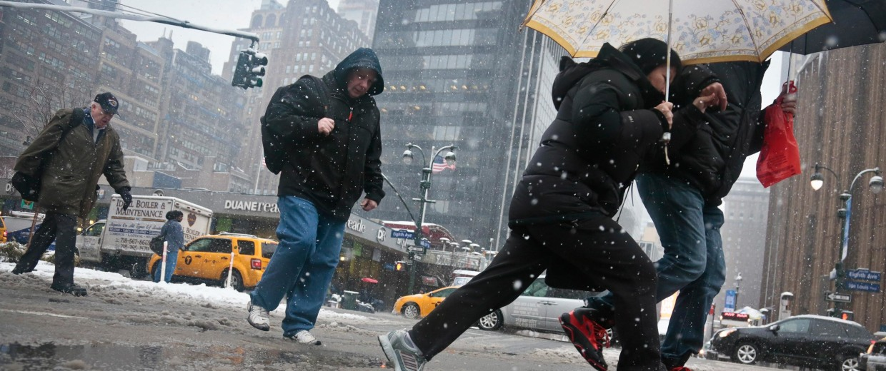 Image: Pedestrians skip over slushy snow in mid-town Manhattan.