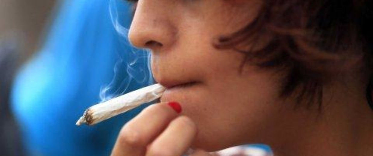 A young woman using a marijuana cigarette