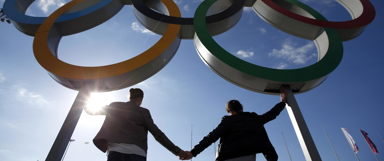 Image: People pose for a picture in front of the Olympic rings at the Olympic Park at the Sochi 2014 Winter Olympics