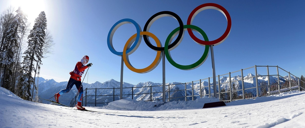 Image: A cross-country skier practices underneath the Olympic rings.