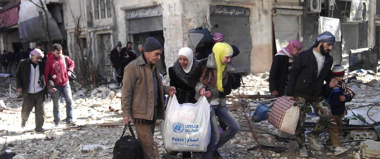 Image: Civilians carry their belongings as they walk towards a meeting point to be evacuated from a besieged area of Homs