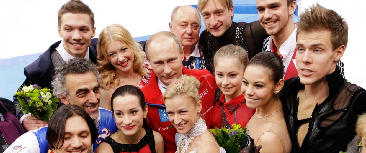 Image: Russian President Vladimir Putin, centre back, poses for a photograph with the Russian team after they placed first in the team figure skating competition