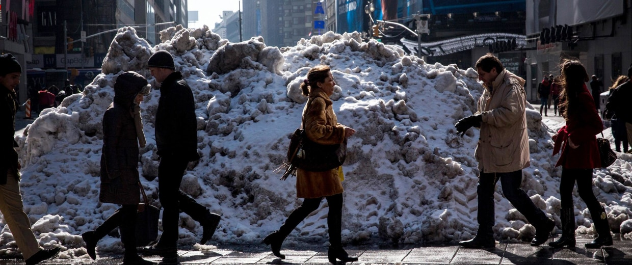 Image: People walk past a pile of snow