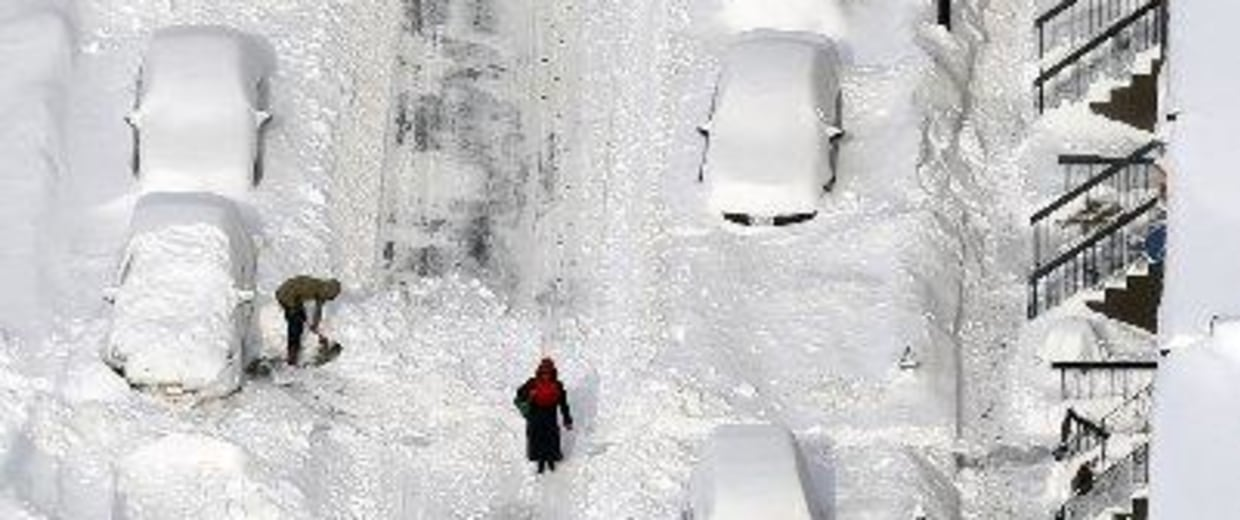 Image: People dig out vehicles buried in snow in downtown Albany, N.Y.
