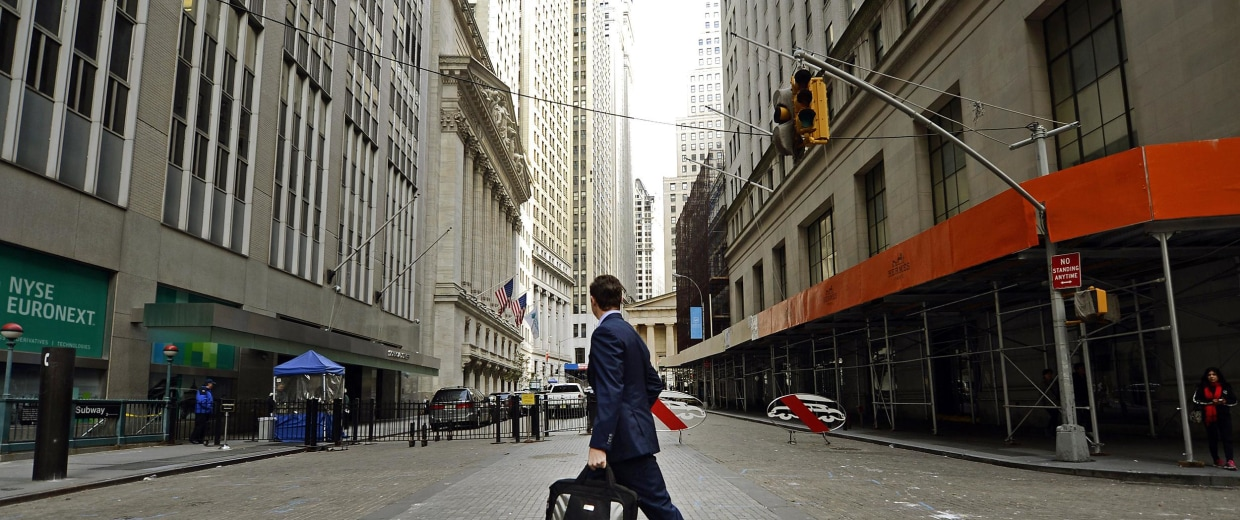 Image: A man looks up towards the New York Stock Exchange as he returns to work on Wall Street in 2012.