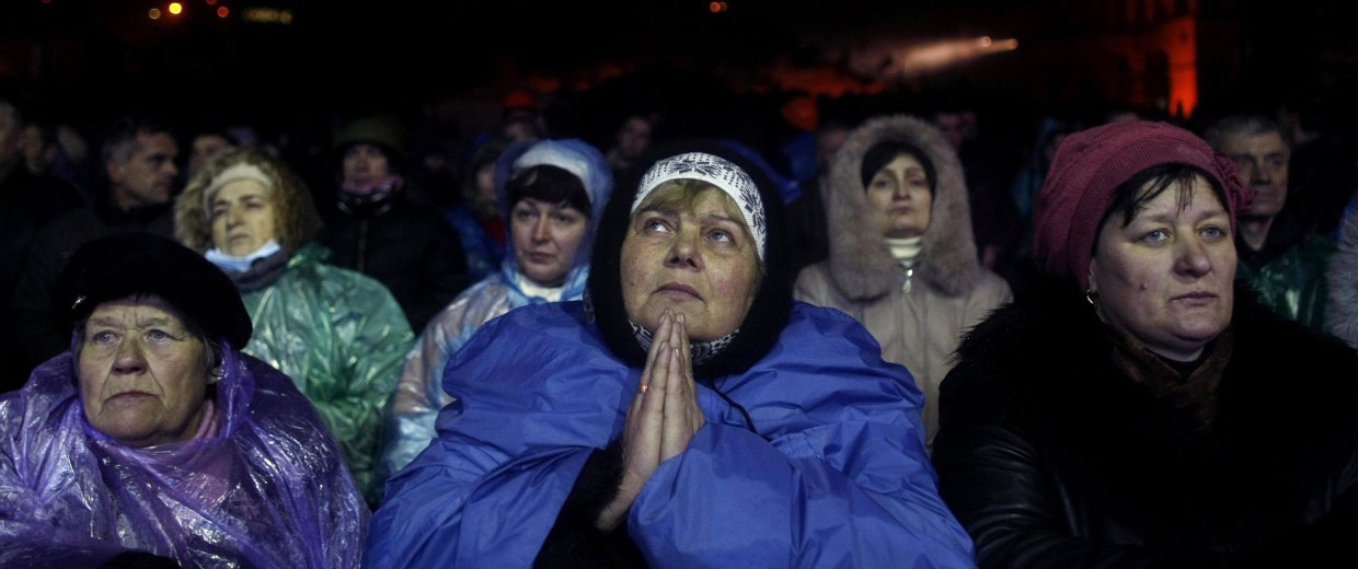 Image: Anti-government protesters pause in prayer at Independence Square in Kiev early on Thursday