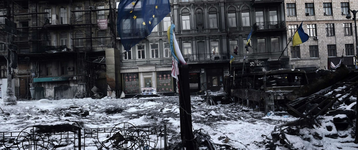 Image: A European Union flag waves near an opposition road block in the center of Kiev