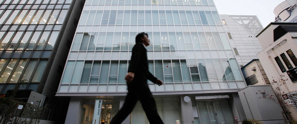 Image: A man walks past a building where Mt. Gox is housed in Tokyo