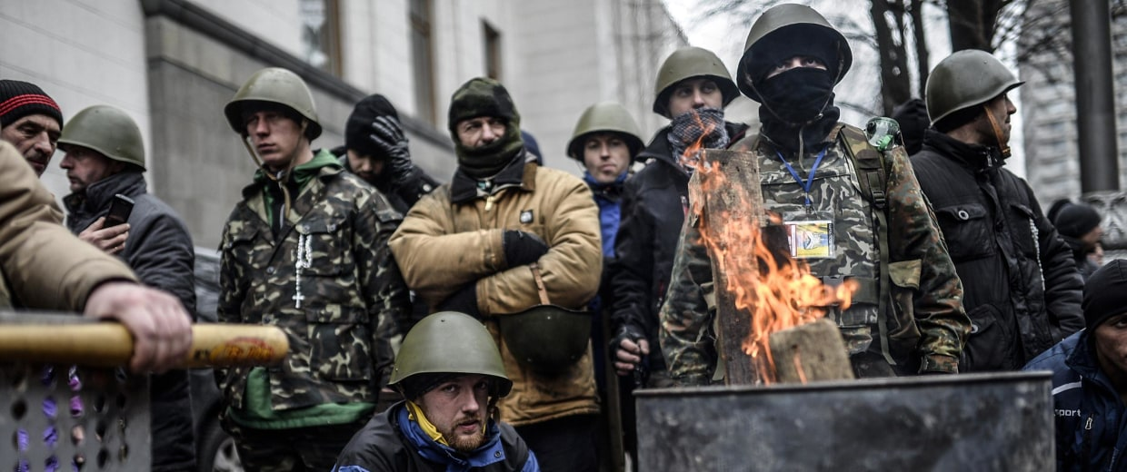 Image: Anti-government protestors wait in front of a parliamentary building in Kiev