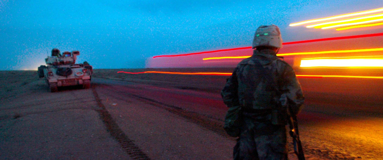 Image: A U.S. Army soldier watches the blur of a convoy.