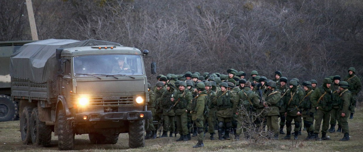 Image: Armed men, believed to be Russian soldiers, assemble near an Ukrainian military base in Perevalnoe
