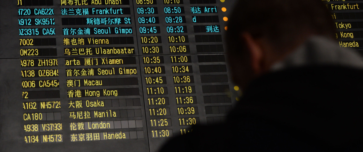 Image: A man stands beside the arrival board showing the flight MH370 at the Beijing Airport