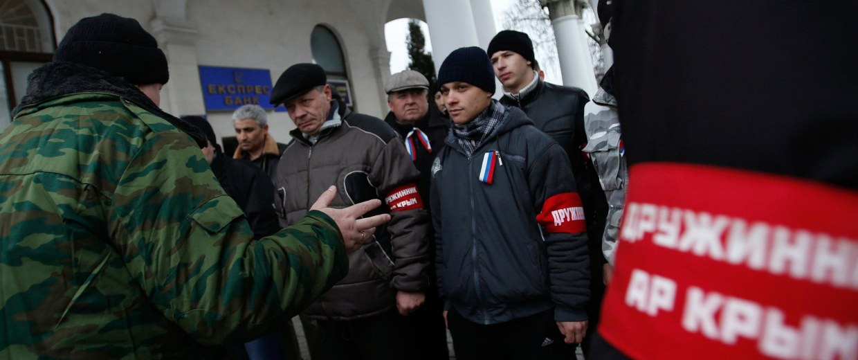 Image: Members of a Crimean self-defense unit get instructions from their commander at the railway station in Simferopol