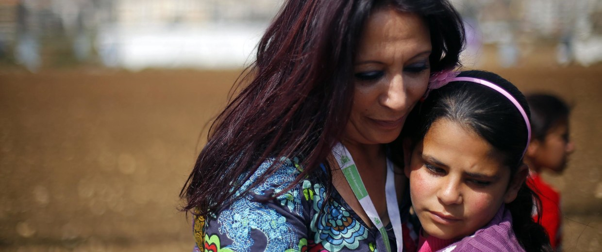 "Image: Fatima, 12, is hugged by  Maria Assi, the director of Lebanese NGO ""Beyond"" in  the Fayda Camp"