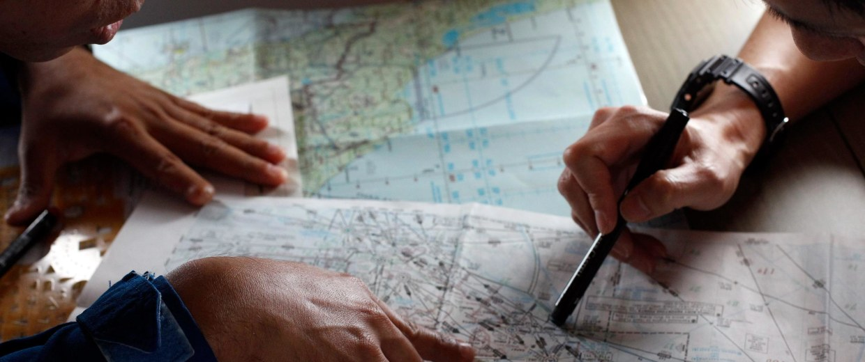 Image:  Japan Coast Guard member studies a map with a Malaysian Maritime Enforcement Agency pilot