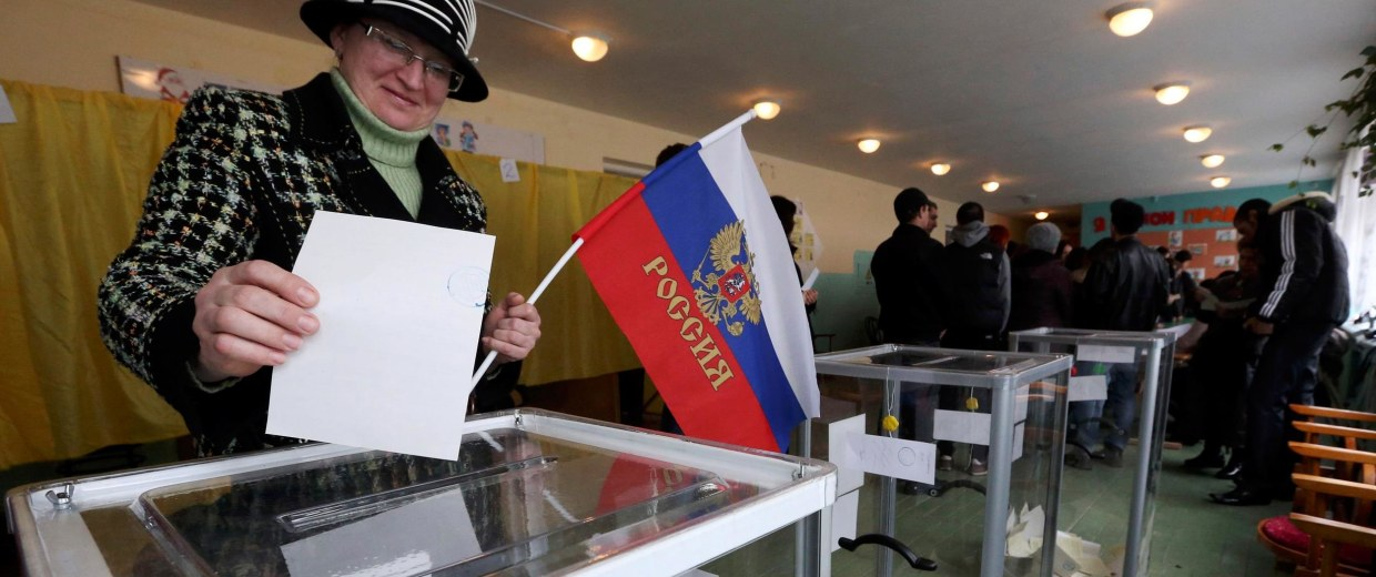Image: A woman holds a Russian flag as she casts her ballot during the referendum on the status of Ukraine's Crimea region at a polling station in Bakhchisaray