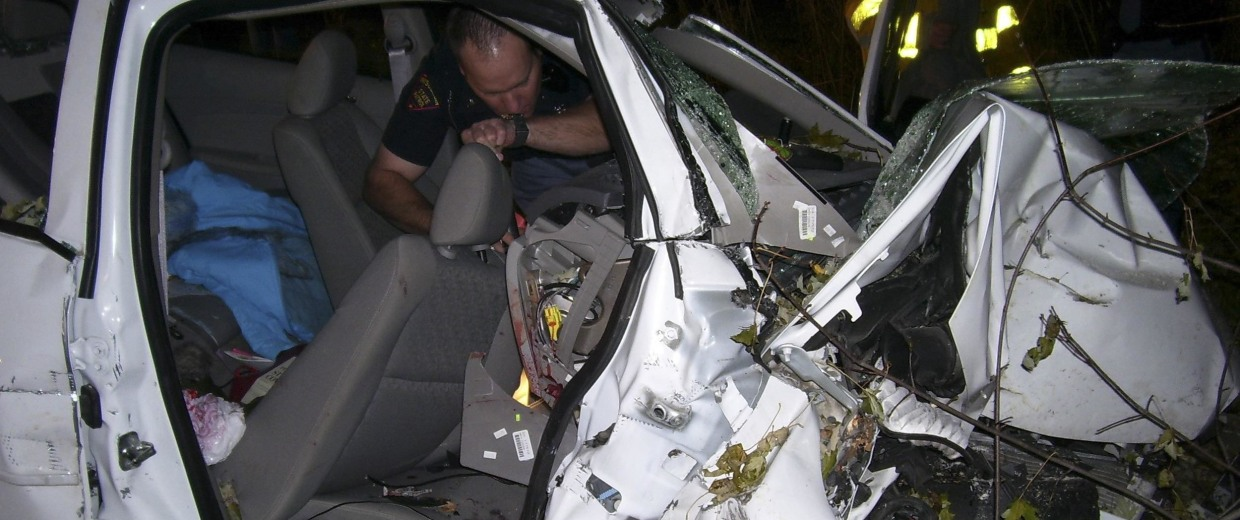 Image: File photo of a police officer looking through the wreck of a 2005 Chevy Cobalt in St Croix County, Wisconsin