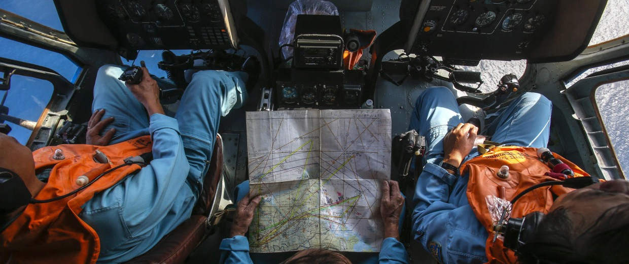 Military personnel work within the cockpit of a helicopter