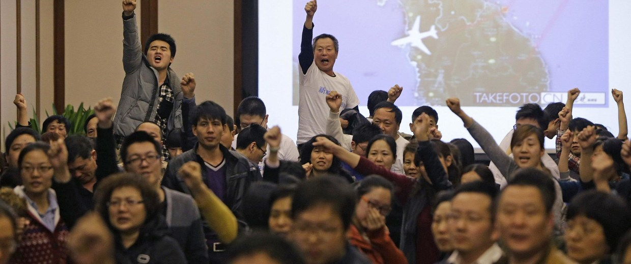 Image: Family members of passengers onboard Malaysia Airlines Flight MH370 raise their fists in Beijing