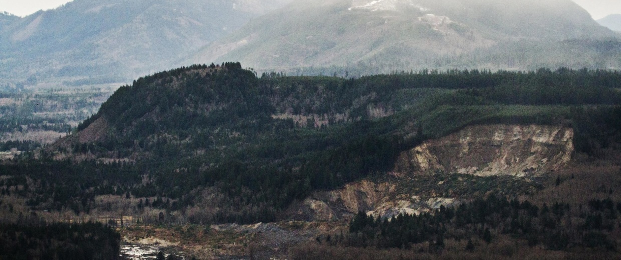 Image: A wide aerial view shows the extensive damage of the landslide after taking out a chunk of earth from the side of the hill facing the Stillaguamish River