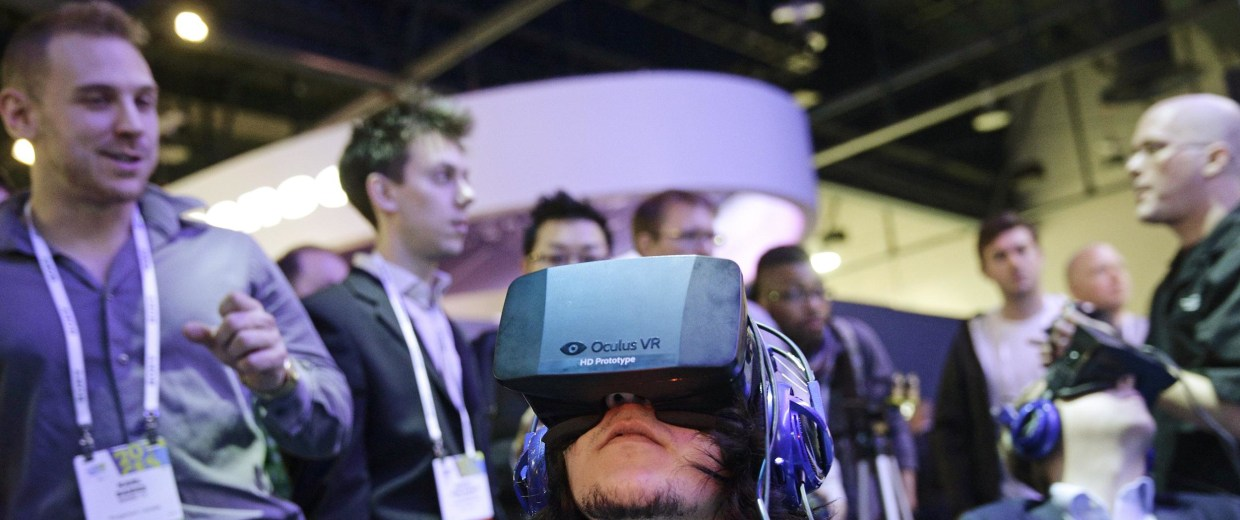 Image: Show attendees play a video game wearing Oculus Rift virtual reality headsets