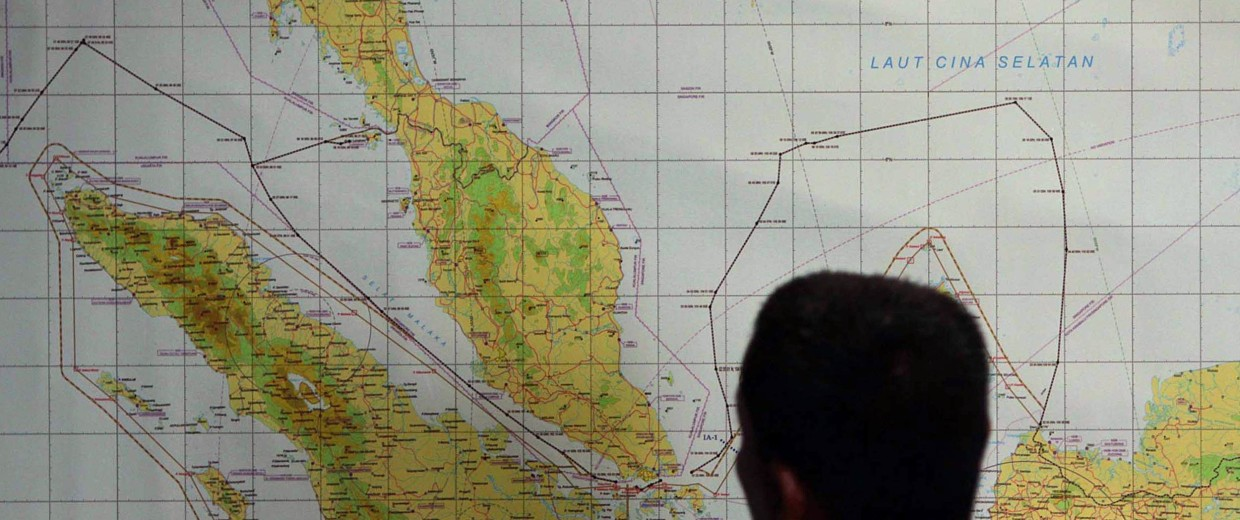 Image: A member of Indonesian Air Force examines a map of of the Malacca Strait