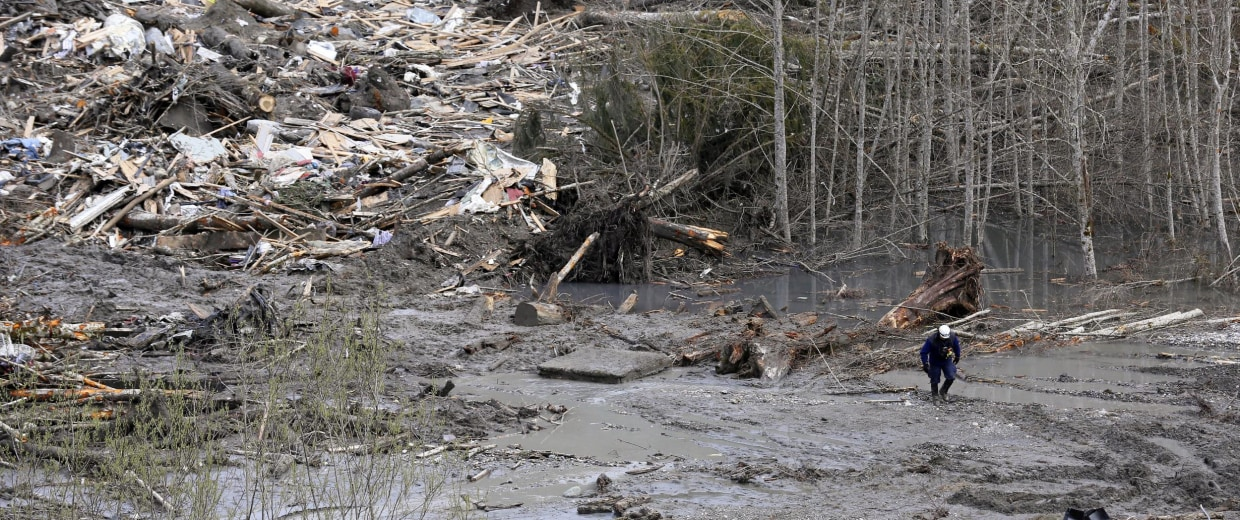 Image: A searcher walks through mud at the scene of a deadly mudslide