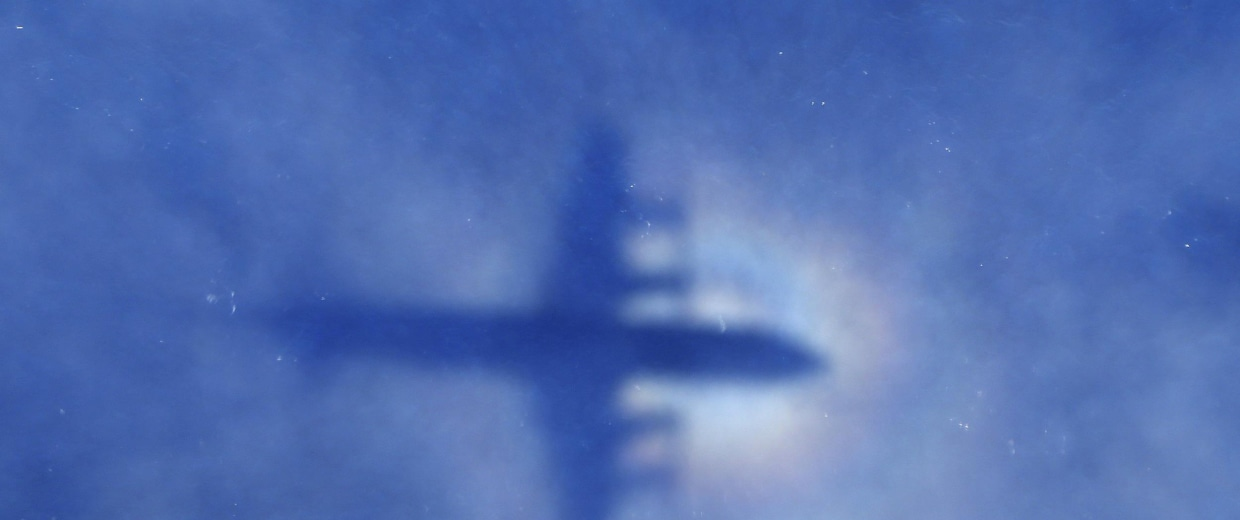Image: The shadow of a Royal New Zealand Air Force P3 Orion aircraft is seen on low cloud cover while it searches for missing Malaysia Airlines Flight MH370
