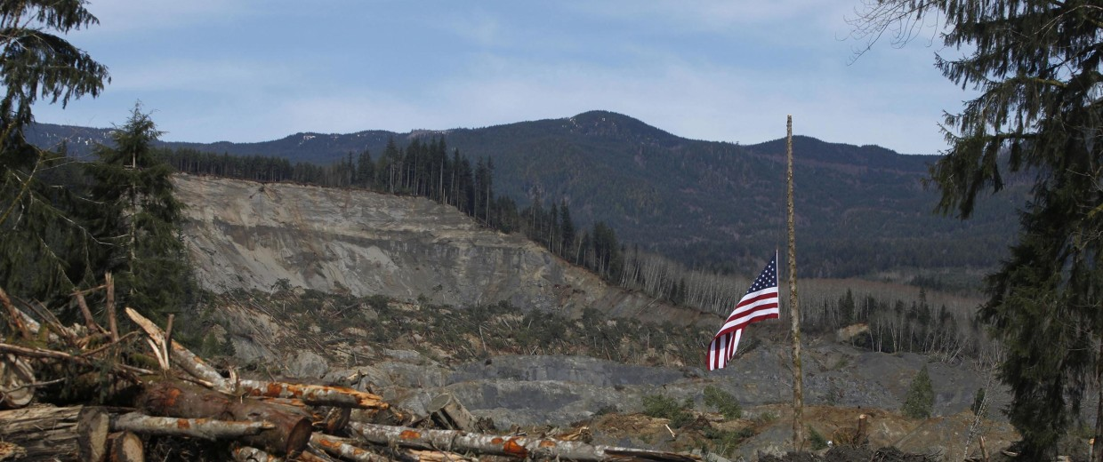 Image: An American flag hangs from the only cedar post left standing at the scene of a deadly mudslide