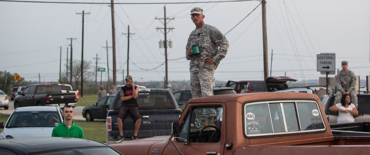 Image: Military personnel and civilians wait in a parking lot outside of the Fort Hood military base