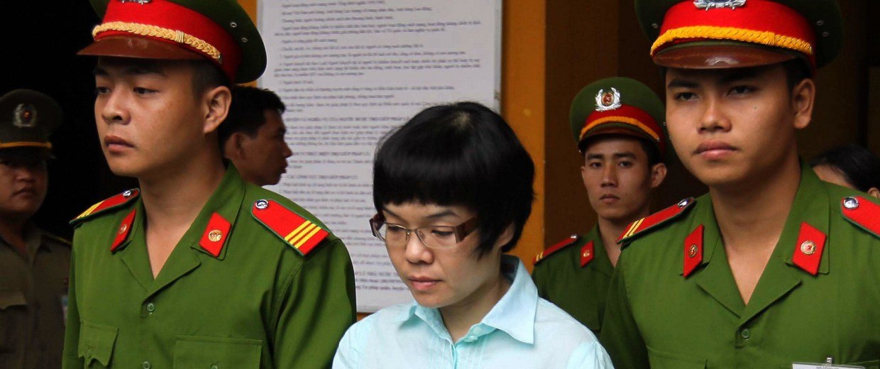 Image: Huynh Thi Huyen Nhu, 37, is led out of the courtroom at a local People's Court House in Ho Chi Minh City