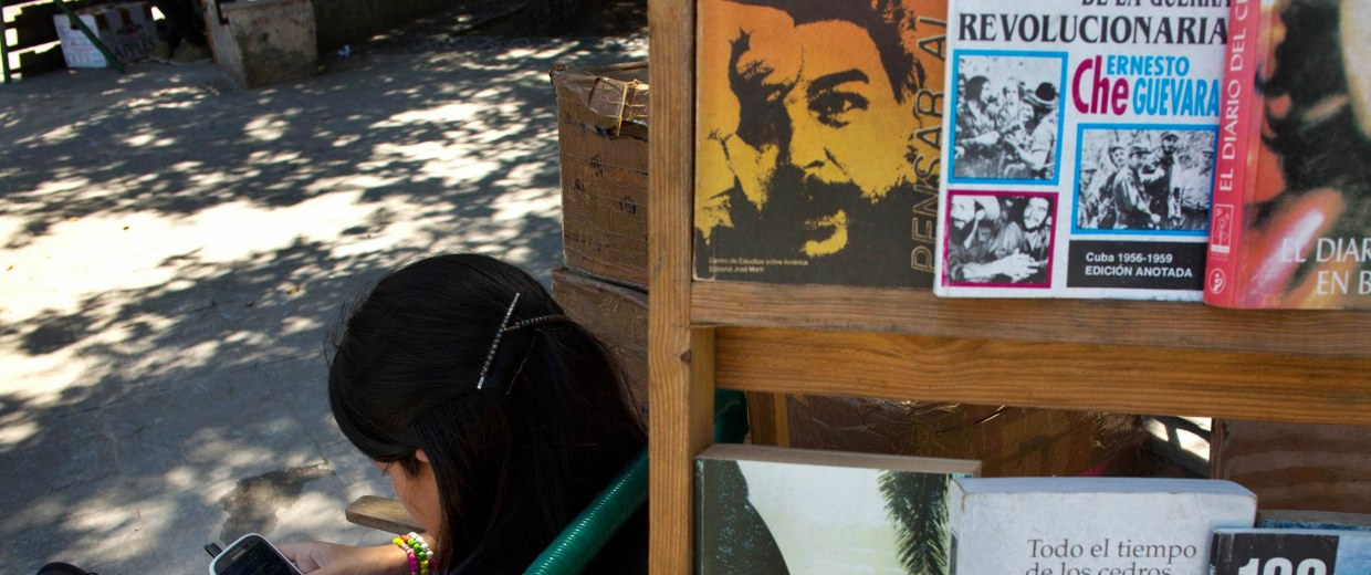 Image: A book street vendor passes the time on her smart phone as she waits for customers in Havana, Cuba