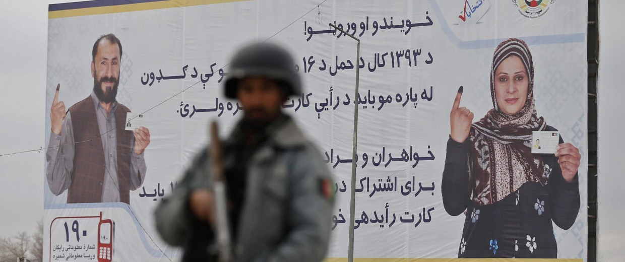 Image: A policeman stands near a billboard for the presidential election at a checkpoint in Kabul