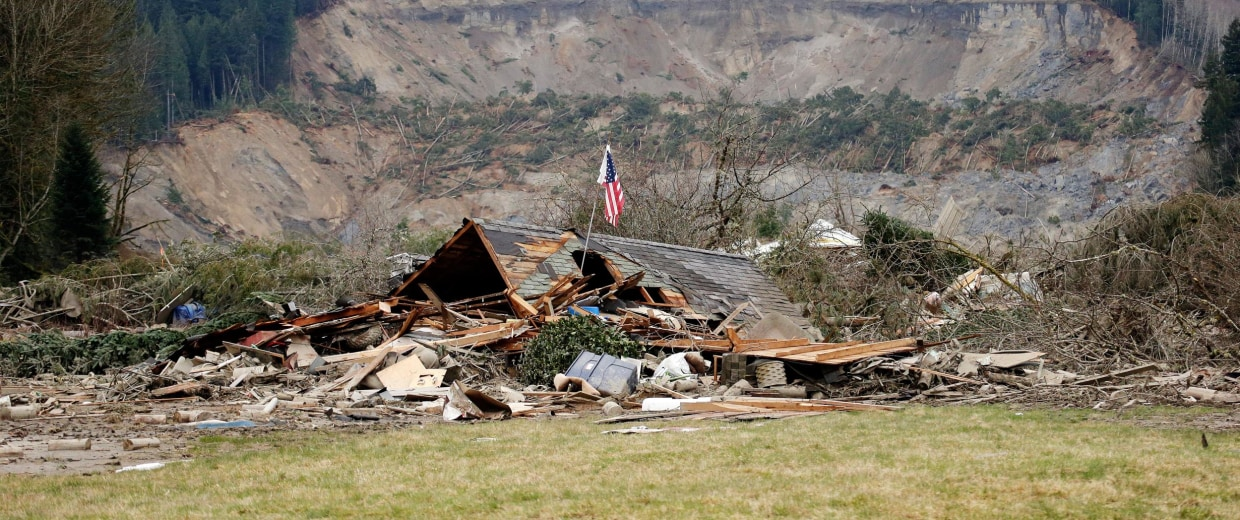 Image: A flag, put up by volunteers helping search the area, stands in the ruins of a home left at the end of a deadly mudslide from the now-barren hillside seen about a mile behind