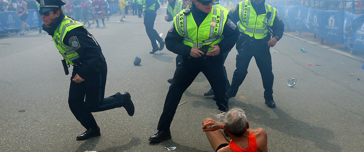 Image: Bill Iffrig, 78, lies on the ground as police officers react to a second explosion at the finish line of the Boston Marathon