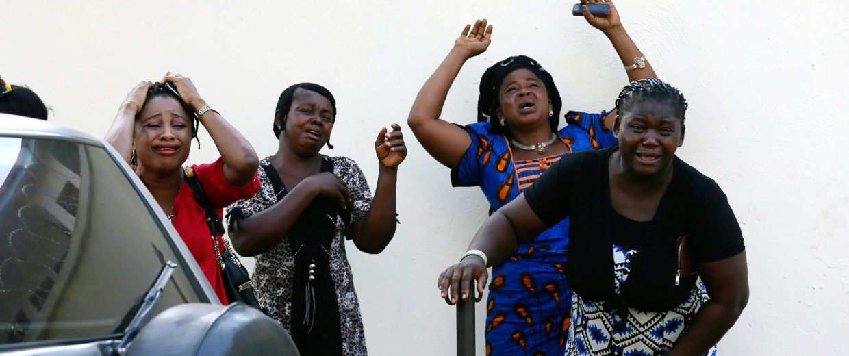 Image: Bystanders react as victims of a bomb blast arrive at the Asokoro General Hospital in Abuja