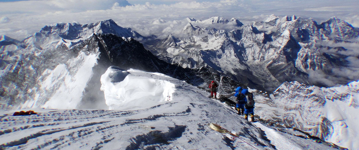 Image: Unidentified mountaineers look out from the summit of Mount Everest