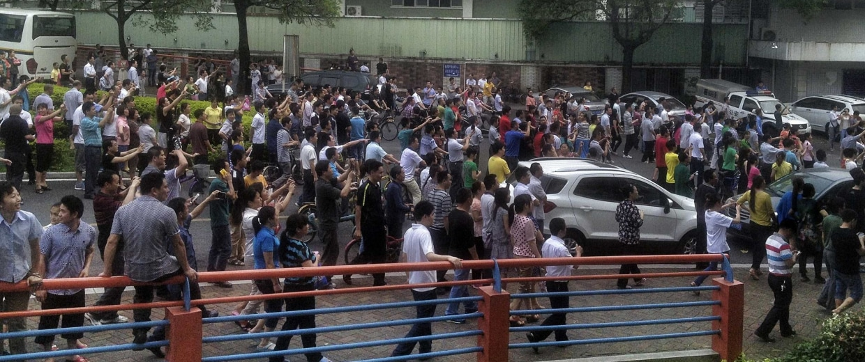 Image: Workers protest during a strike at Yue Yuen Industrial