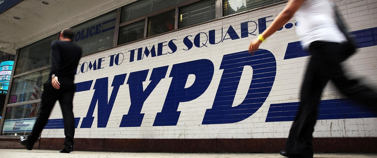 Image: People walk by an NYPD outpost in Times Square